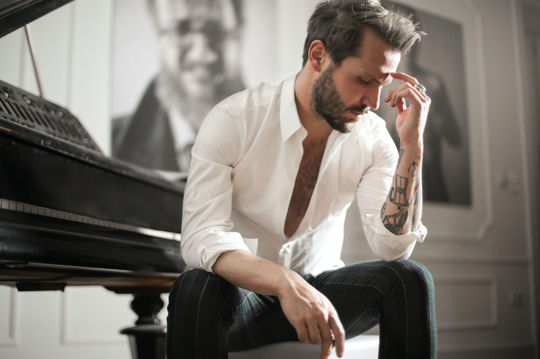 dramatic tattooed male sitting at piano